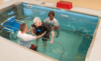 Trainers helping a person train in pool