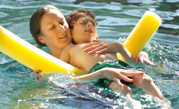 Person helping child float in pool