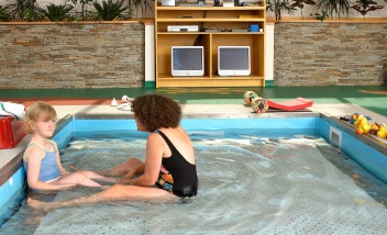 Adult and child sitting in shallow pool