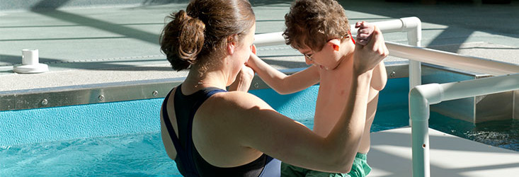 Adult doing water therapy with child