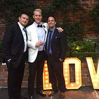 Three people in suits and bow ties posing for photo