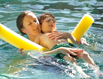 Person holding child on floating device in pool