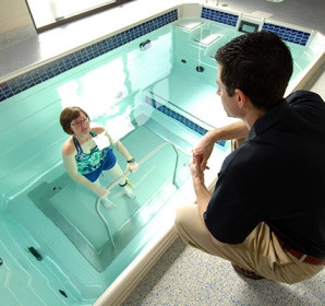 Trainer instructing trainee in pool