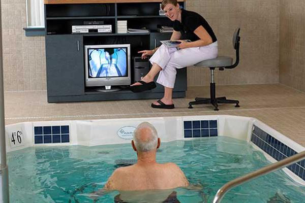 Trainer instrcuting Pool trainee with tv display