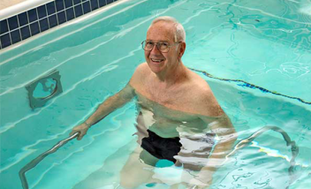 Person standing in pool holding metal bars