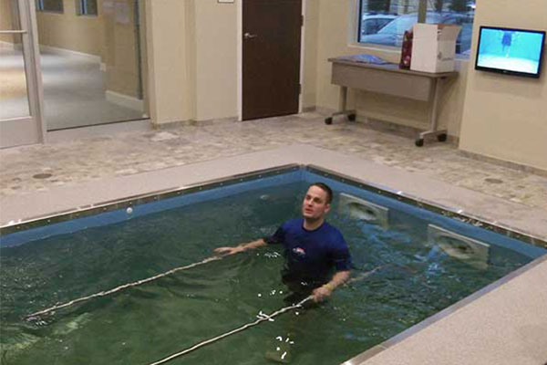 Person in HydroWorx pool with metal bars