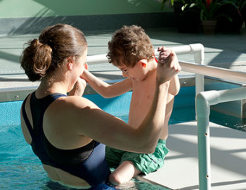 Person holding child on platform by pool
