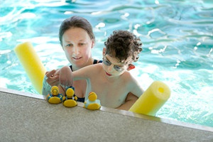 Person holding child in pool with rubber ducks